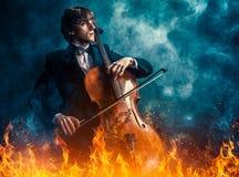 Violoncelista no fogo fotografia de stock royalty free