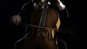 Violoncelista que joga uma composição musical Fundo preto video estoque