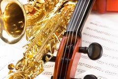 Violoncell som trimmar pinnor och den skinande alt- saxofonen Arkivfoto