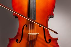 Violoncello with bow stick on the grey background. Violoncello with bow stick view on the grey background royalty free stock photos