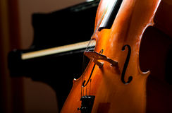 Violoncello. Close up and piano in the background royalty free stock photography