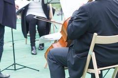 Violoncellspelarecellisten i en fri utomhus- konsert på ett offentligt parkerar, musikerlekvioloncellen fotografering för bildbyråer