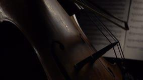 Violoncelo en el arco oscuro del arco en las secuencias detrás de las notas Cierre para arriba Vista lateral almacen de video