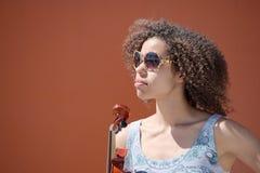 Violoniste féminin avec des lunettes de soleil regardant fixement dans la distance Image libre de droits