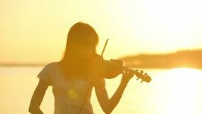 Violoniste féminin jouant le violon au lac au coucher du soleil banque de vidéos