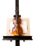 Viool die zich bij het schilderen van geïsoleerde schildersezel bevindt Stock Foto
