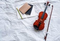 Viool en boog gezet naast geopend boek en potlood, op de achtergrond van de grungeoppervlakte stock foto