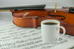 Viool en kop van koffie op muziekblad Stock Fotografie