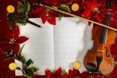 Viool en open muziekmanuscript op de rode achtergrond Kerstmistak en klokken Stock Afbeeldingen