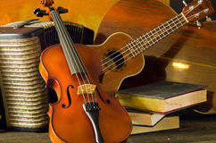 Viool, gitaar en boeken op stilleven houten achtergrond Royalty-vrije Stock Foto