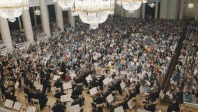 Vioolorkest het spelen op scène van oude concertzaal voor veel mensen stock footage