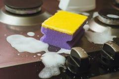 Viooltje - gele spons met een metaalgasfornuis Het schoonmaken van het vuil met een spons met schuim royalty-vrije stock afbeeldingen