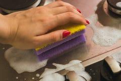 Viooltje - gele spons met een metaalgasfornuis Het schoonmaken van het vuil met een spons met schuim royalty-vrije stock fotografie