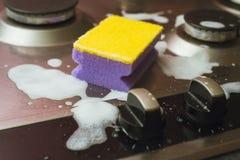 Viooltje - gele spons met een metaalgasfornuis Het schoonmaken van het vuil met een spons met schuim stock foto's