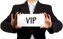 Vip. Businesswoman in a black jacket and a white shirt shows a card with the inscription vip. Girl on a white background. Selective focus Stock Image