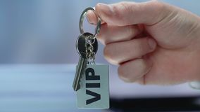 VIP inscription on keychain in businessman hand, luxury resort for rich customer. Stock footage stock video
