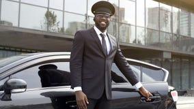 Vip-Passagiertaxifahrer, der höflich Autotür für seinen Kunden, besten Service öffnet stockfotografie