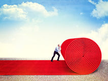 Vip way. Man roll huge red carpet Royalty Free Stock Photo