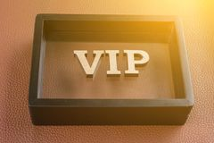 VIP is written in abstract letters in black frame. Brown leather textured background. VIP is written in abstract letters in a black frame. Brown leather textured Stock Image