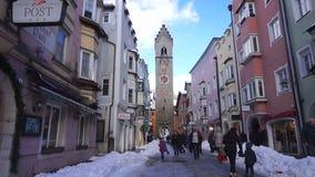VIPITENO WŁOCHY, STYCZEŃ, - 23, 2018: Zwölferturm ludzie w głównej ulicie stary średniowieczny miasteczko Vipiteno i wierza zbiory wideo