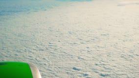 Vippa på ner skott av en grön flygplanmotor som flyger över moln arkivfilmer