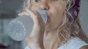Vippa på upp av trött hög kvinna med grått hårdricksvatten från sportflaskan, medan gå på trampkvarnen i idrottshall close arkivfoton