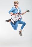 Vippa som hoppar en sida i studio, medan spela gitarren Royaltyfri Foto
