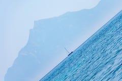 Vippad på sikt av en segelbåt på horisonten, med den Mount Athos loomien Royaltyfria Bilder