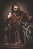 Viquingue irritado com espada em um guerreiro tradicional veste-se, levantando em um fundo escuro foto de stock royalty free