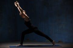 做Virabhadrasana的美丽的瑜伽妇女1个姿势 免版税图库摄影