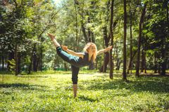 Virabhadrasana III Asanas de yoga en nature Le yoga pose quotidien Jeune femme de pratique Yoga en stationnement photographie stock