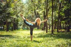 Virabhadrasana III Yogaasanas in aard De yoga stelt elke dag Praktizerende jonge vrouw Yoga in het park stock fotografie