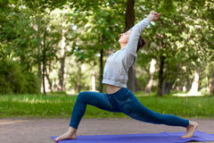 48 Virabhadrasana 1 pose in park alley. Serene beautiful sporty young woman working out on blue mat on the street in park alley, doing high lunge exercise stock photo