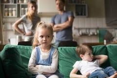Virada da menina da criança, ofendida ou furada ignorando pais e irmão fotos de stock royalty free