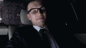 Virada do homem de negócios após o telefonema que senta-se no banco traseiro do carro, conduzindo em casa video estoque