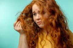 A virada e a mulher com seu cabelo seco danificado enfrentam o fundo do azul da expressão fotos de stock royalty free
