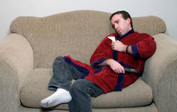 Viral Infection. Young male with a viral infection relaxing on the couch watching tv Royalty Free Stock Image