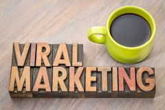 Viral marketing word abstract in wood type. Viral marketing word abstract in vintage letterpresss wood type with a cup of coffee Royalty Free Stock Image