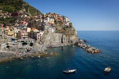 Vire hacia el lado de babor con los barcos y el turista de pesca, en fondo las casas coloridas de Manarola, Cinque Terre, Liguria imagen de archivo