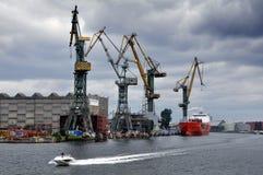 Vire las grúas hacia el lado de babor que se colocan a lo largo de la orilla del mar Báltico Foto de archivo libre de regalías