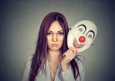 Vire a mulher preocupada com expressão triste que descola a máscara do palhaço fotografia de stock royalty free