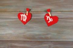 Virgem e Capricórnio sinais do zodíaco e do coração backg de madeira imagem de stock royalty free