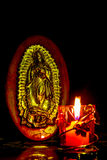 Virgen de Guadalupe At the Light of a candle. The Virgins image of Guadalupe carved on a wood illuminated with the candlelight on a black background Stock Photo