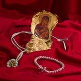 Virgen y guirnalda en una lona roja Imagenes de archivo