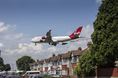 Virgin Atlantic Plane Landing over houses. Virgin Atlantic Boeing 747 flying over houses on approach to Heathrow airport.  The debate over expanding Heathrow is Royalty Free Stock Image