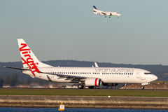 Virgin Australia Airlines Boeing 737-800 aircraft at Sydney Airport with a REX Saab 340 landing behind. Royalty Free Stock Image