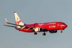 Virgin Blue flygbolag Boeing 737-8FE VH-VOL på inställningen som ska landas på Melbourne den internationella flygplatsen Royaltyfri Bild