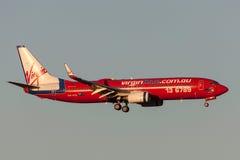 Virgin Blue flygbolag Boeing 737-8FE VH-VOL på inställningen som ska landas på Melbourne den internationella flygplatsen Arkivfoton