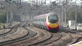Virgin Mainline train. Moving through a small station stock footage