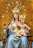 Virgin Mary with baby Jesus, crowned, blessing. A detailed view of a statue of the Virgin Mary with baby Jesus, blessing, against a niche with a golden mosaic Royalty Free Stock Images